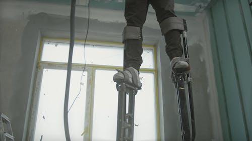 A Man Using Drywall Stilts