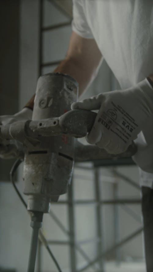 Worker Mixing Paint in Bucket
