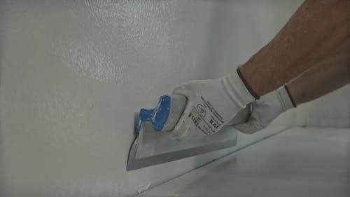 Man Smoothening Walls for Painting