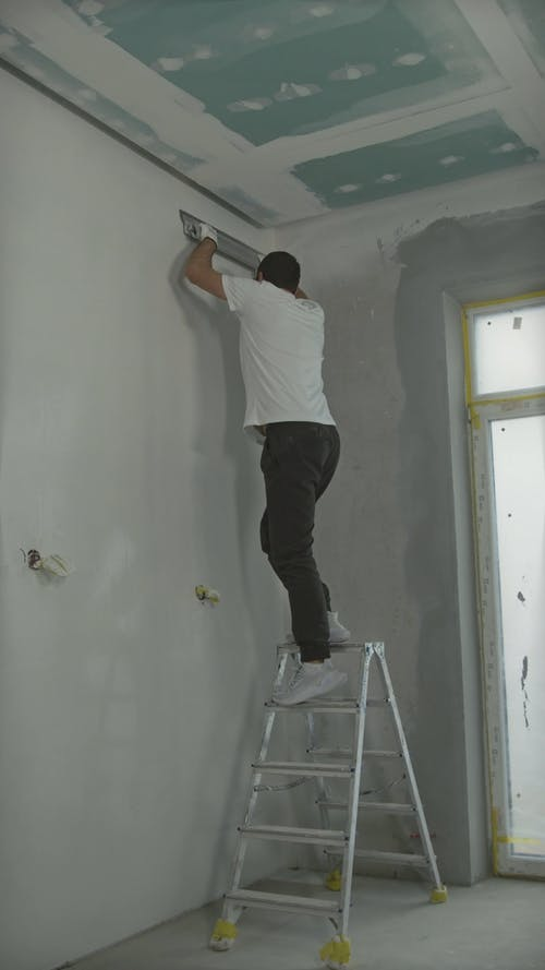 Worker Making Walls Smooth with Putty
