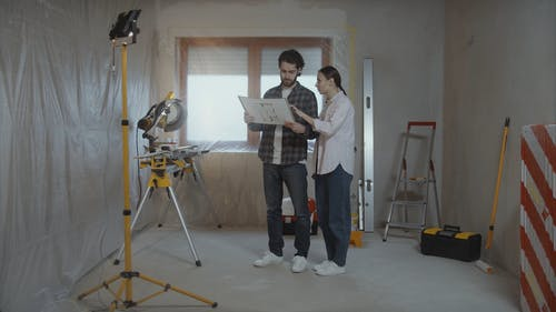 Man and Woman Talking about Home Renovation with Blueprint in Hand