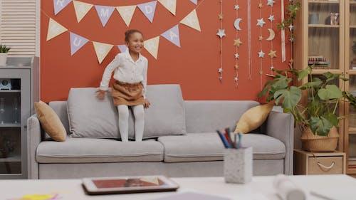 Young Girl Jumping On Sofa