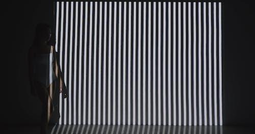 Woman Walking in Striped Shadow
