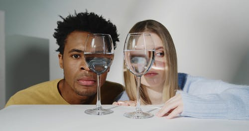 Man and Woman Looking Through Glass of Water