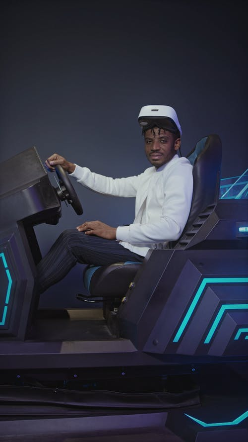 Man Seated In A Game Simulator