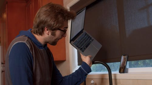 Man Showing Laptop to Person in Video Call
