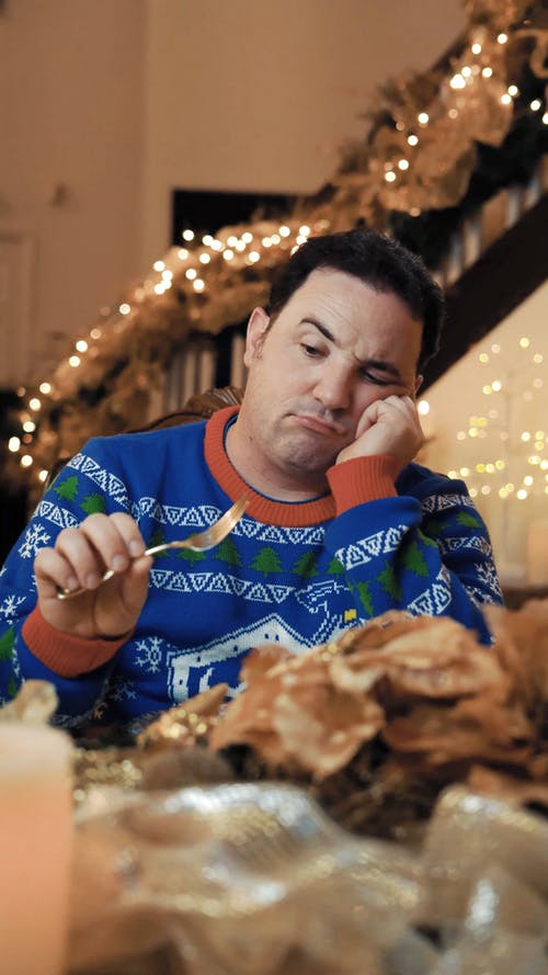 Bored Guy Looking at Silverware on Christmas