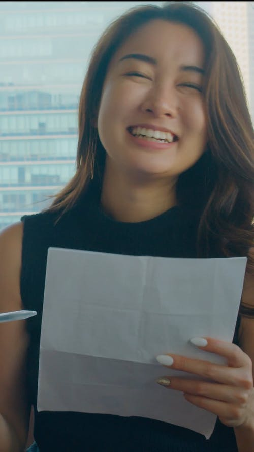 A Happy Woman Holding a Pen and Paper