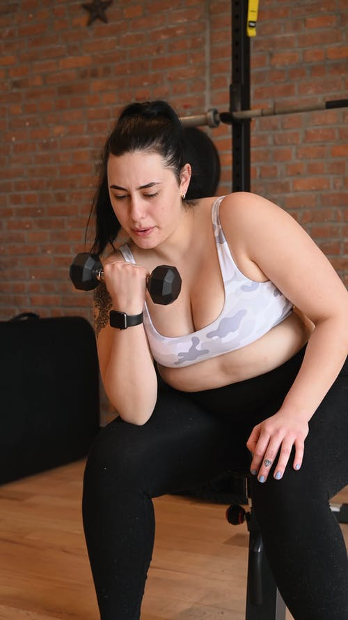 Woman Lifting Dumbbell while Sitting