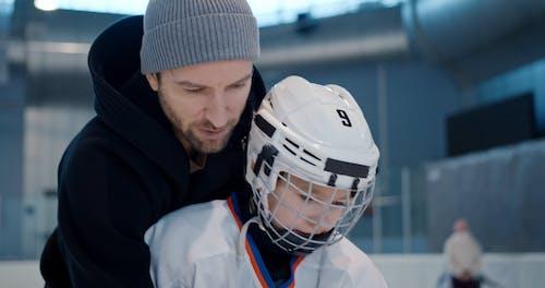 Man Teaching Ice Hockey to a Boy