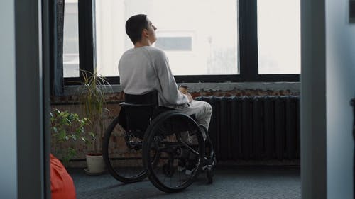 Person with Disability Drinking Coffee by the Glass Window