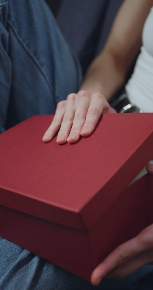 A Person Opening a Box Containing a Cloth