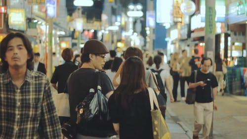 Couple Holding Hands While Walking on a Busy Street