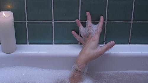 A Person Running Her Fingers on a Bathtub Edge