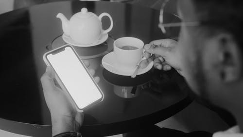 Man Holding his Mobile Phone and Tea