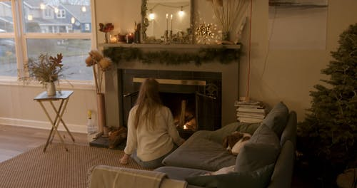 Woman Putting Wood Logs in Fireplace