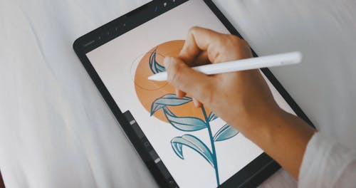 Person Editing Picture on Digital Tablet