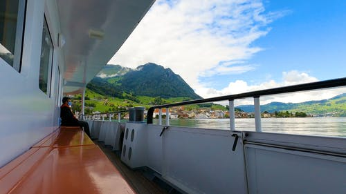 Man on Ferry Boat Looking at Mountain Landscape