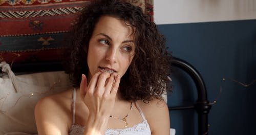 A Woman Touching her Lips in Bed