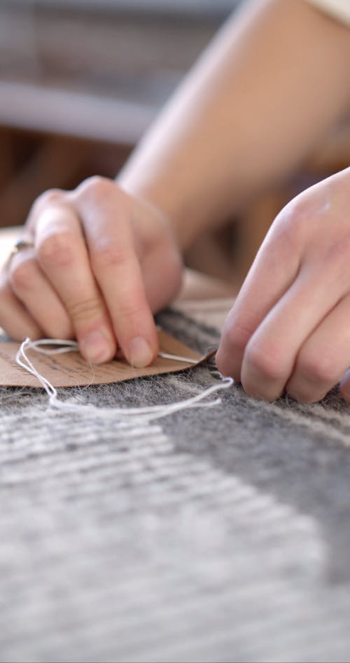 Person Sewing a Label Tag on a Woven Fabric