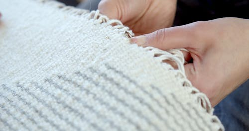 Person Sewing a Metal Piece on a Woven Fabric