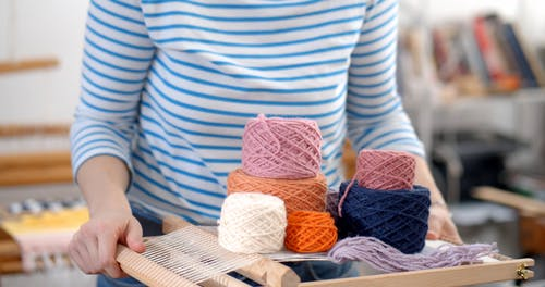 Woman Holding Small Weaving Loom and Balls of Yarn