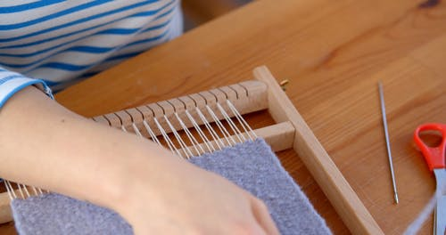 A Person Weaving on a Frame Loom