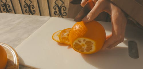 Person Peeling an Orange with Knife