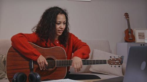 Woman Having a Video Call while Using a Guitar