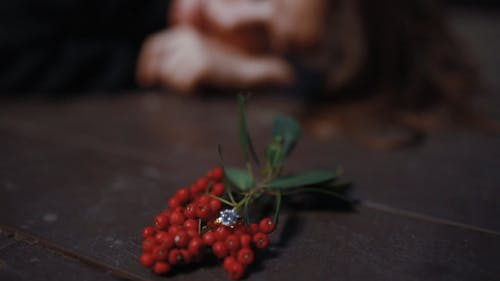 Woman Crying on the Floor Next To Red Berries
