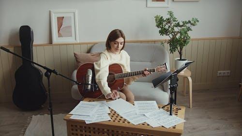 Woman Teaching How to Play Guitar