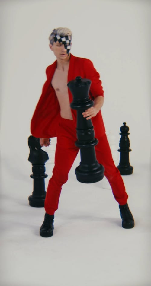 A Man Dancing with Giant Chess Pieces