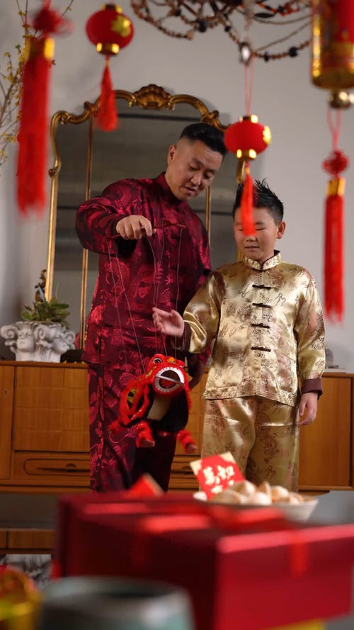 A Father And Son Playing With A Lion Dance Puppet