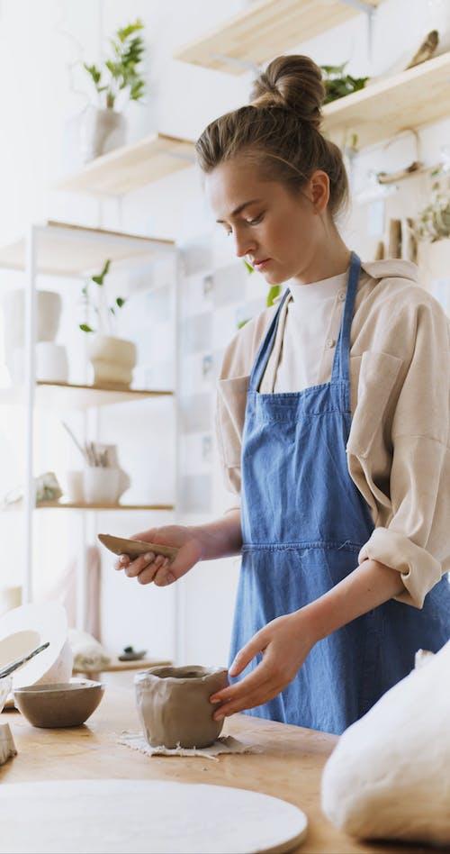 A Woman Molding a Clay into a Pot
