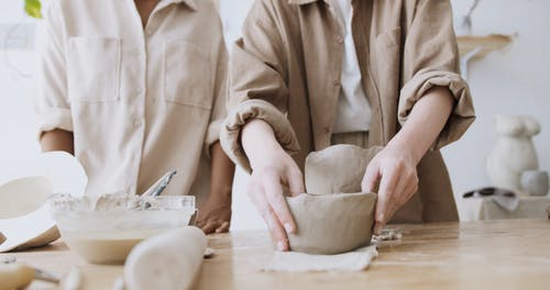 Women Making a Clay Figurine