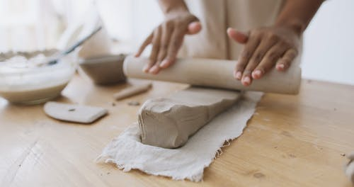 Woman Flattening a Clay with a Rolling Pin