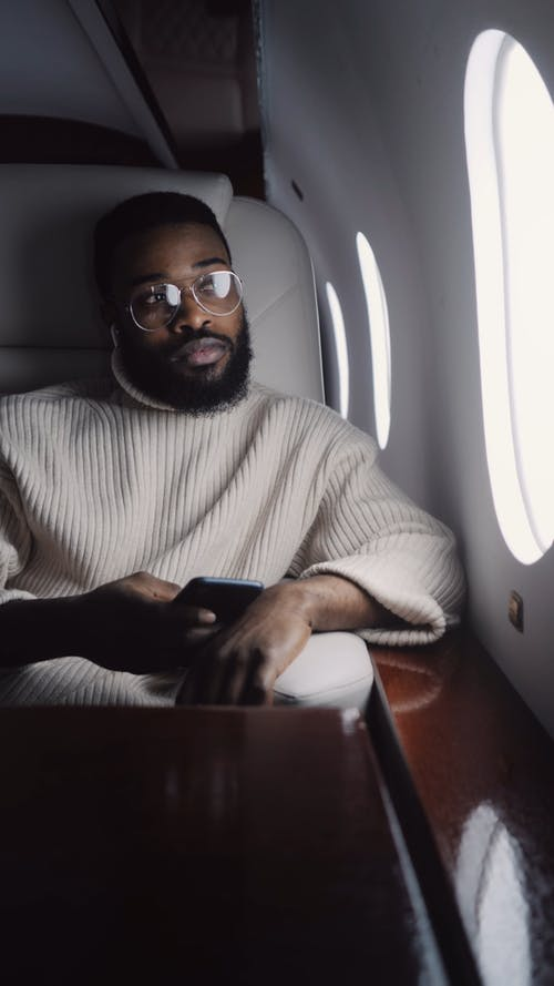 Guy Listening to Music while Sitting in an Airplane