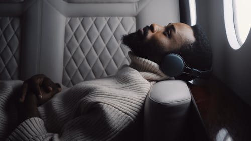 Man Wearing a Wireless Headphones while Lying on a Jet