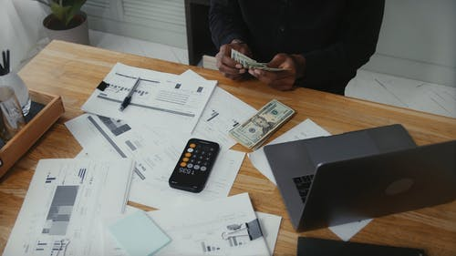 Man Counting Money on Work Desk