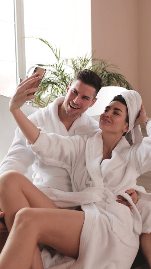 Couple Wearing Bathrobe Taking Pictures beside a Bathtub