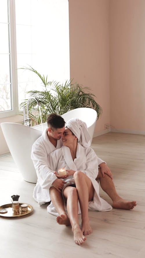 Couple Wearing Bathrobe Sitting Beside the Bathtub