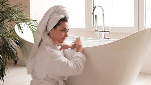 Woman Sitting beside her Bathtub