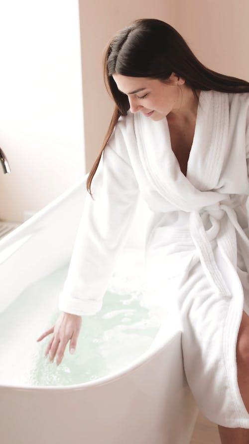 Woman Preparing her Bath in the Bathtub