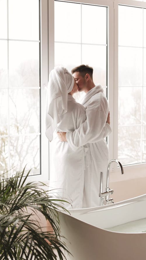 A Couple Wearing Bathrobes Kissing and Hugging