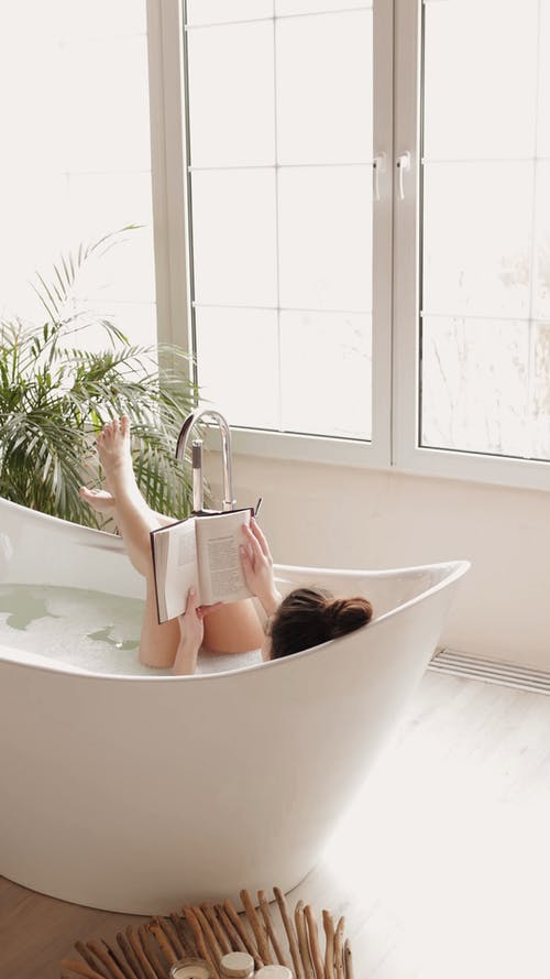 Woman Reading a Book while Lying Down in a Bathtub