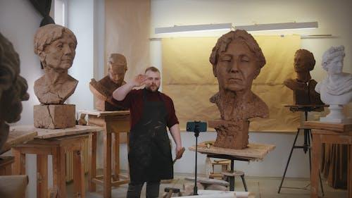Man Recording Video Beside A Sculpture