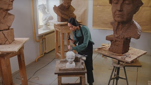 Woman Using Hammer and Chisel on Sculpture