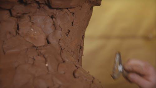 A Man Sculpting a Clay