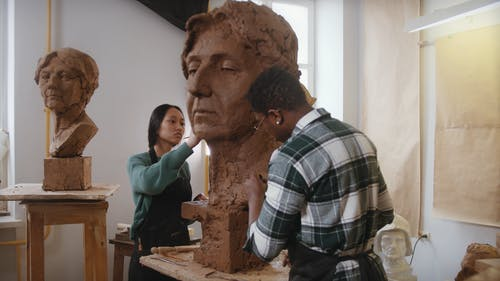 A Man and a Woman Sculpting a Clay