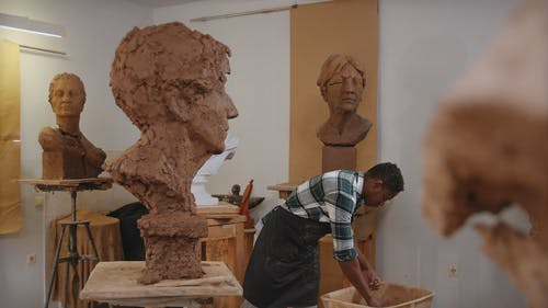 A Man Making Sculpture From a Clay
